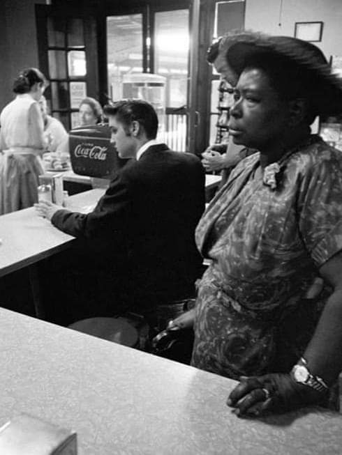 Elvis sits to eat at a segregated lunch counter while an elderly black woman stands, waiting for food to take away. she's not allowed to sit there.