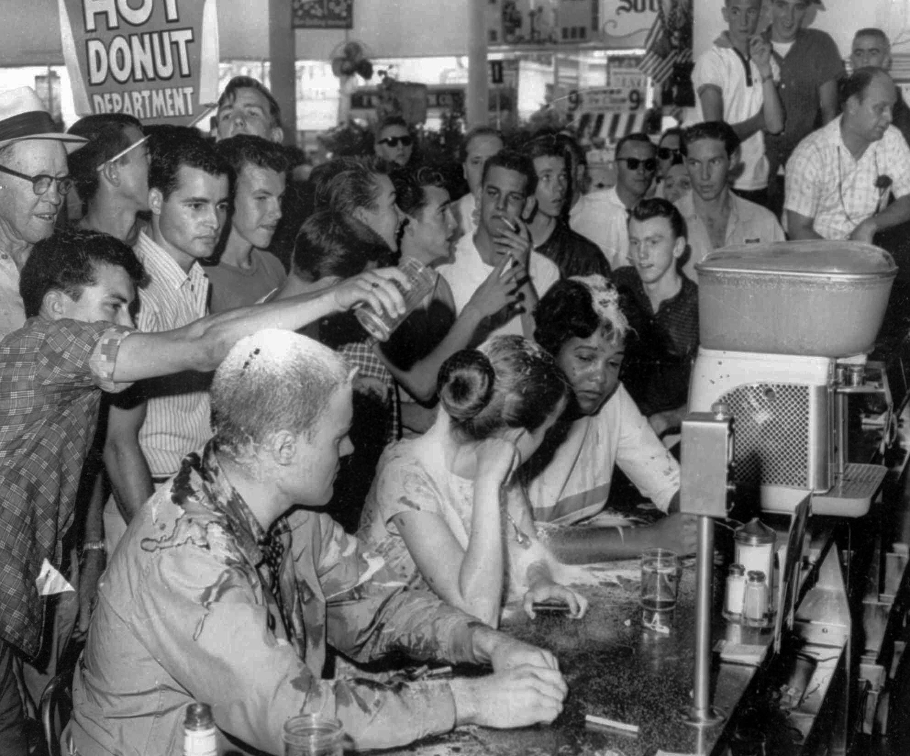 FILE - In this May 28, 1963 file photo, a group of whites pour sugar, ketchup and mustard over the heads of Tougaloo College student demonstrators at a sit-in demonstration at a Woolworth's lunch counter in Jackson, Miss. Seated at the counter, from left, are Tougaloo College professor John Salter,and students Joan Trumpauer and Anne Moody. John Salter, who also used the name John Hunter Gray, died Monday, Jan. 7, 2019 at his home in Pocatello, Idaho.  Relatives say he was 84 when he died Monday after an illness. (Fred Blackwell/The Clarion-Ledger via AP, File) ORG XMIT: MSJAD701